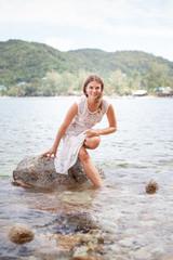 beautiful young blonde woman walking near the sea in a white dress