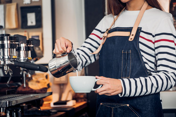 Asia woman barista pour milk into hot coffee cup at counter bar in front of machine in cafe restaurant,Food business owner concept.
