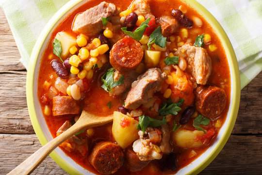 Cachupa stew with meat, chorizo and vegetables close-up in a plate. horizontal top view