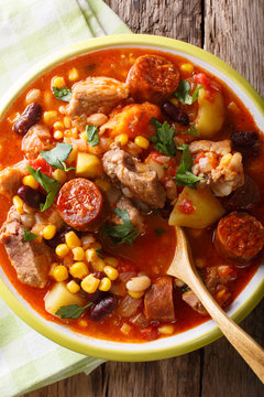 Cachupa stew with meat, chorizo and vegetables close-up in a plate. Vertical top view