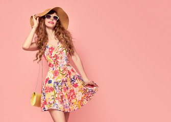 Portrait of Fashion Young woman in Floral Dress. Pretty Girl in Hat, Sunglasses. Female model in Stylish Summer Outfit. Pink Yellow Vanilla Color. Beautiful Lady. Vintage