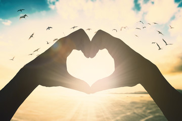 Hand make heart shape over sunset beach background concept for praise and worship  freedom life background.