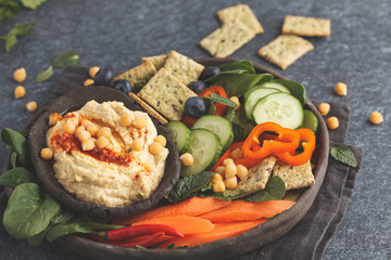 Homemade traditional hummus with vegetables, crackers on a black clay dish, dark background, top view. Healthy vegan food concept.