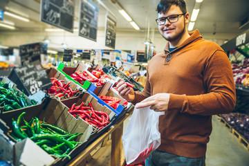 man choose red hot pepper in market