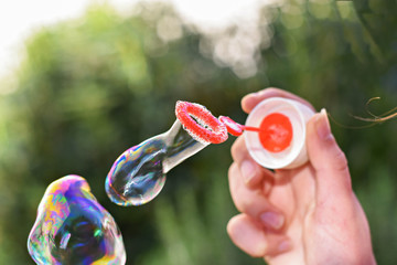 Girl blowing soap bubbles on green grass natural background.