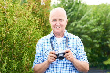 Portrait of smiling senior man taking pictures in park using vintage photo camera while travelling and looking at camera