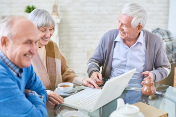 Portrait of three modern senior people using laptop in retirement home and smiling happily, copy space