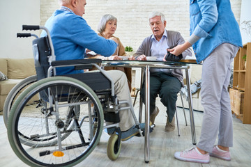 Full length portrait of group of senior people playing board games sitting round table in retirement home, copy space