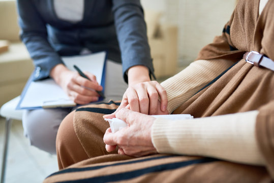 Close up of female psychologist holding hand of senior woman during therapy session, copy space