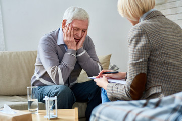 Portrait of depressed senior man sharing problems during therapy session with female psychiatrist writing on clipboard