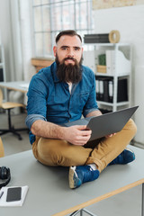 Bearded man sitting on office desk with laptop