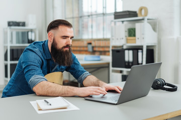 Casual bearded man sitting working on a laptop