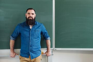 Male teacher standing in front of a chalkboard