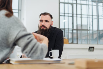 Bearded businessman listening to a colleague