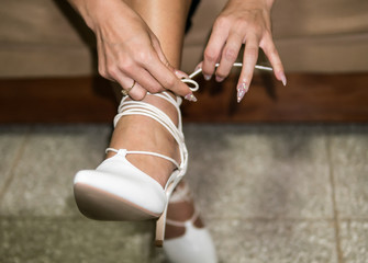 Woman with pointy decorated nails tying lace up heels.
