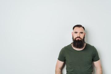 Young serious bearded man wearing a t-shirt