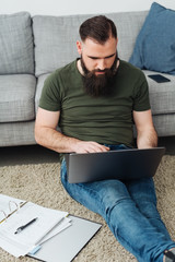 Man working with laptop on floor next to sofa