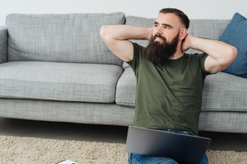 Bearded man relaxing on carpet with laptop