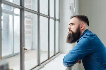 Thoughtful bearded man staring out of a window