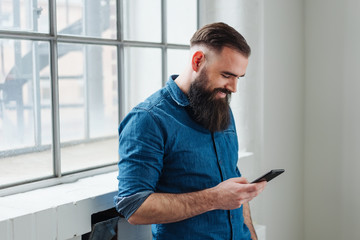 Smiling man reading a text message on his mobile