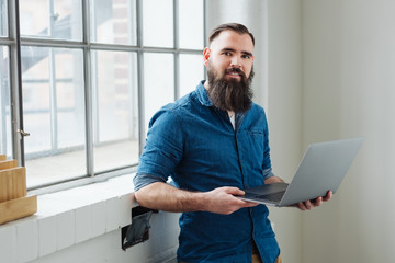 Relaxed bearded man using a handheld laptop