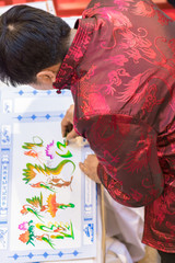 Chinese man in traditional clothes draws a picture, top view