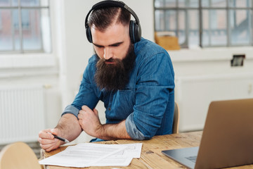 Businessman wearing headphones and reading