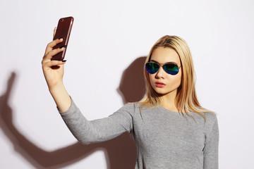 Pretty hipster girl making selfie over white background.
