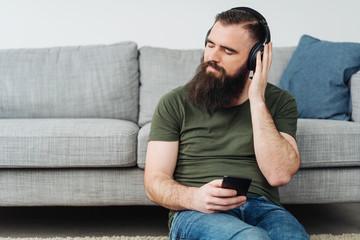 Bearded man sitting listening to music