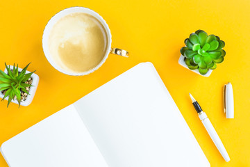 Workplace with bklonotom, pen, cup of coffee and green whiskers in white pots. On a bright yellow background. Top view. Flat lay