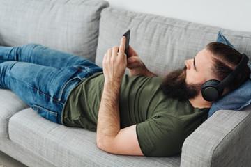 Bearded man with headphones using phone on sofa