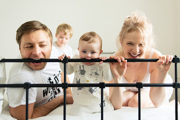 Teething baby, young family on bed