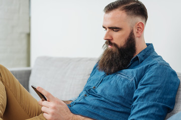 Bearded man with mobile phone sitting on sofa