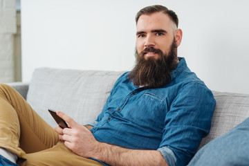 Smiling bearded man with mobile phone on sofa