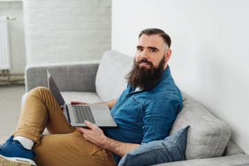 Smiling bearded man sitting on sofa with laptop