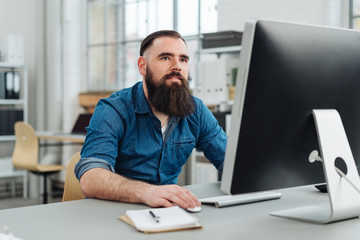 Bearded man sitting in front of monitor at office