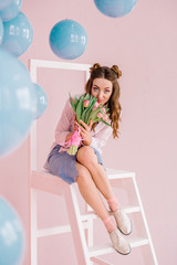 A girl in a blue dress and a pink shirt sits on a ladder in a pink room with a bouquet of tulips