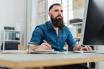 Bearded man looking at monitor in office work