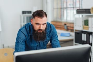 Businessman standing reading a desktop monitor