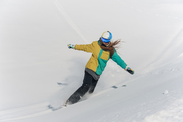 Female snowboarder in colorful sportswear and helmet riding down the powder snow hill