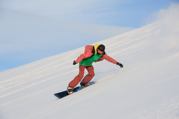 Active snowboarder in sportswear riding on the snowy slope