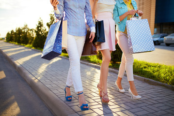Beautiful girls with packages after shopping A picture of a group of happy friends shopping in the city. Girls walking around the city after shopping. good mood. Evening light. shopping concept