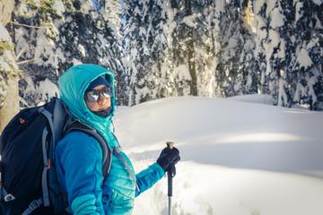 A Hiker trekking in winter woods.