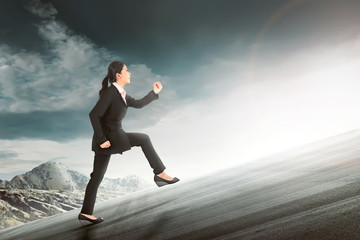 Pretty asian business woman running to climb a hill
