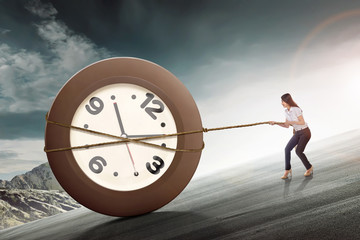 Young asian business woman pulling clock with rope
