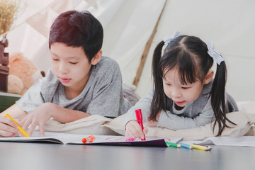 Happy Asian little cute girl and boy drawing and painting color on notebook in a white room background.