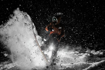 Freeride snowboarder jumping on the board in snow at night