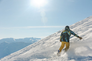 Back view of male freeride snowboarder sliding down the snowy hill