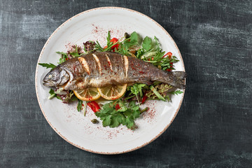 Hot fresh delicious roasted whole trout barbecue with fresh herbs and lemon, on a wooden background top view close-up