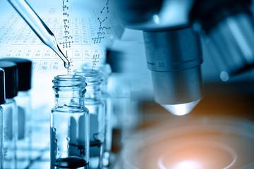 Microscope with laboratory glassware, blue tone